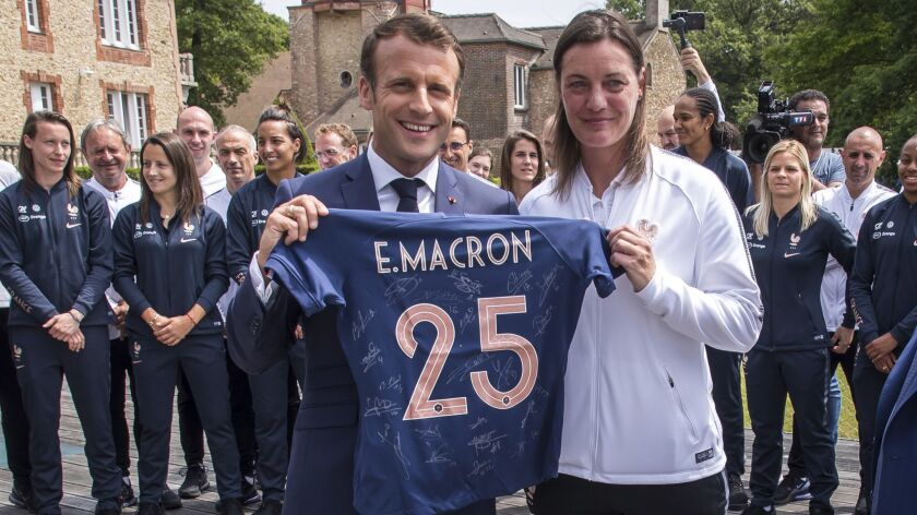 French President Emmanuel Macron, left, poses with a French National Women's Soccer team's jersey ne