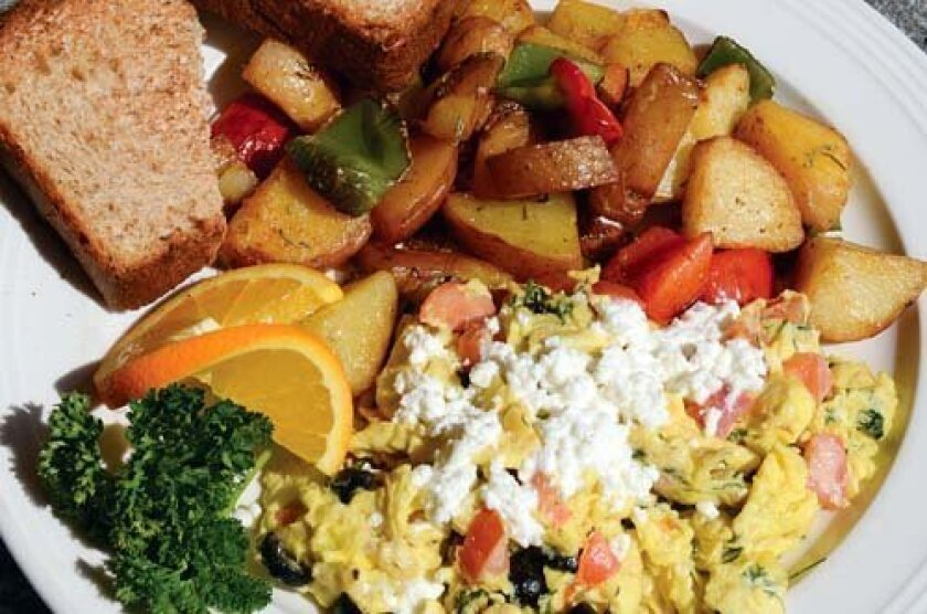he Mediterranean Scramble contains feta cheese, tomatoes, black olives and dill, and is served with potatoes and homemade whole-wheat bread. Photos by Kelley Carlson