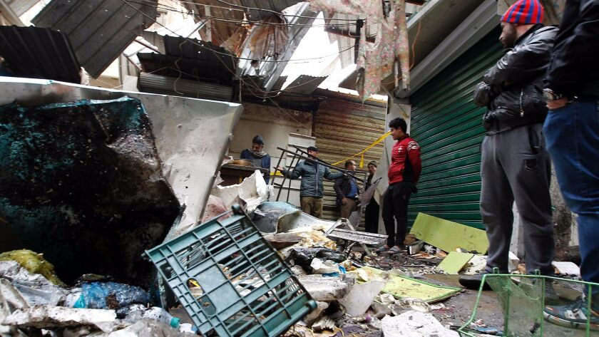 Iraqis observe the aftermath of a double blast in a busy Baghdad market.