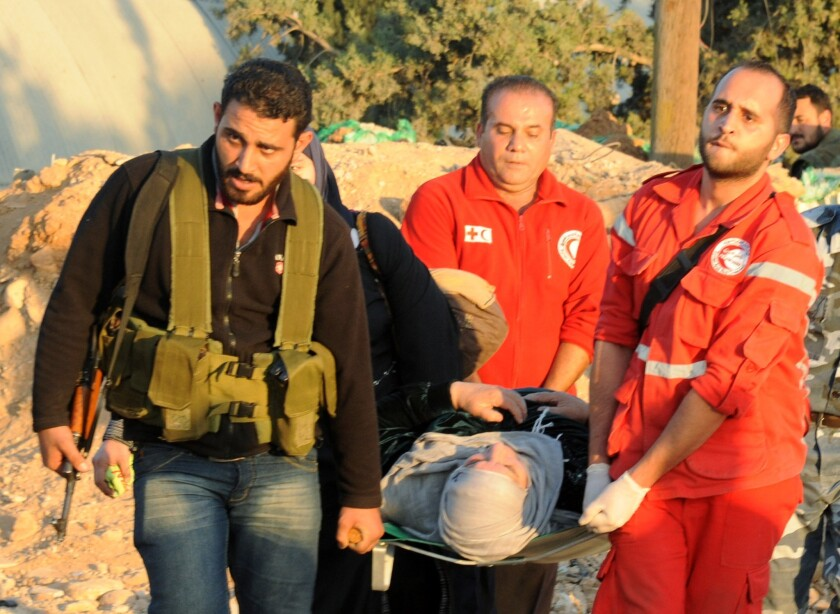 A fighter joins Red Crescent volunteers carrying a woman on a stretcher during an evacuation of residents of a Damascus suburb that has been under siege for months.