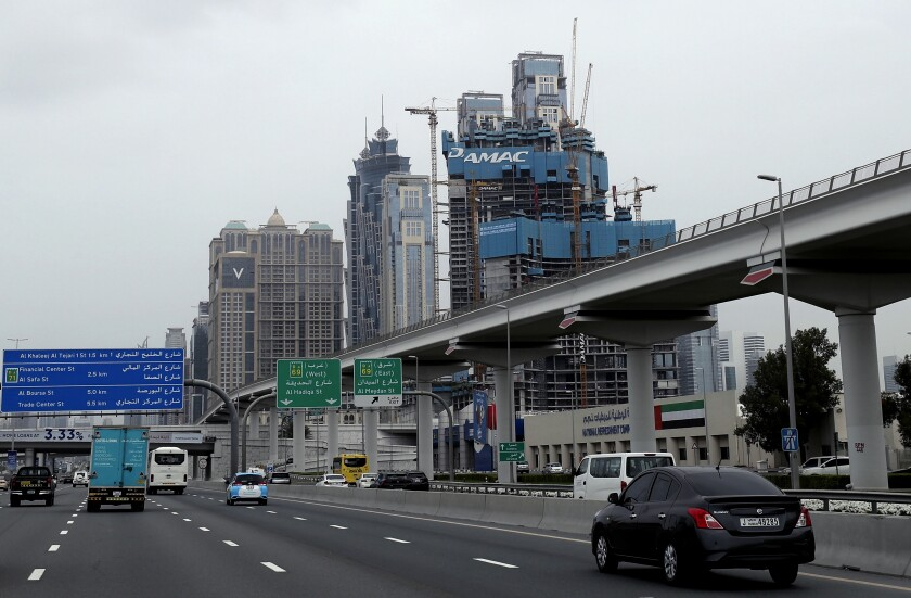FILE - In this Feb. 11, 2020, file photo, cars pass by the under construction DAMAC towers on Sheikh Zayed highway in Dubai, United Arab Emirates. A Dubai real-estate company DAMAC Properties, known for its deals with former President Donald Trump, said, Thursday, Sept. 23, 2021, it has received regulator approval for an effort to take the firm private. (AP Photo/Kamran Jebreili, File)