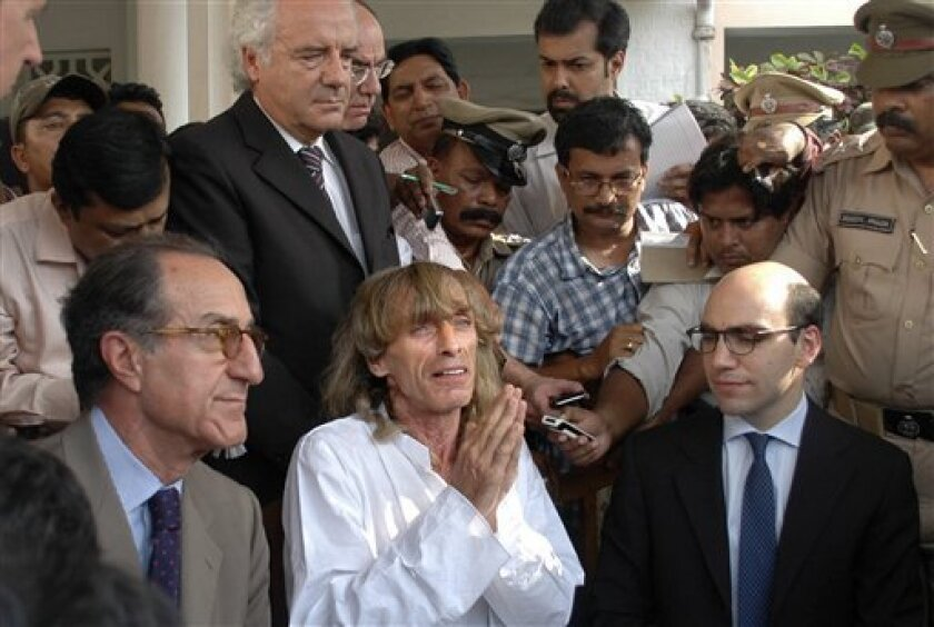 Italian tourist guide Paulo Bosusco, center, who was abducted by Maoist rebels more than a month ago, talks to the media, as unidentified Italian officials sit near him outside the state guest house in the eastern Indian city of Bhubaneswar, India, Thursday, April 12, 2012. Maoist rebels on Thursday released Bosusco from a remote forest area of eastern India after the state government agreed to release five rebels from prison. Basusco, along with Italian tourist Claudio Colangelo, was abducted on March 14 while on a trek in Orissa state. Colangelo was released 11 days later, but Basusco remained in captivity while negotiations took place between the rebels and the government. (AP Photo)