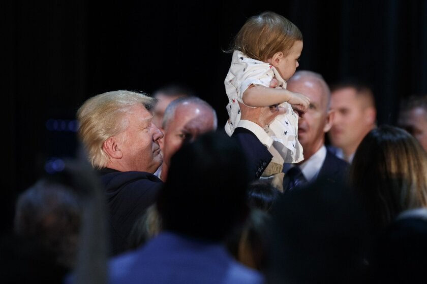 Republican presidential candidate Donald Trump lifts a child after delivering a policy speech on child care, Tuesday, Sept. 13, 2016, in Aston, Penn. (AP Photo/Evan Vucci)