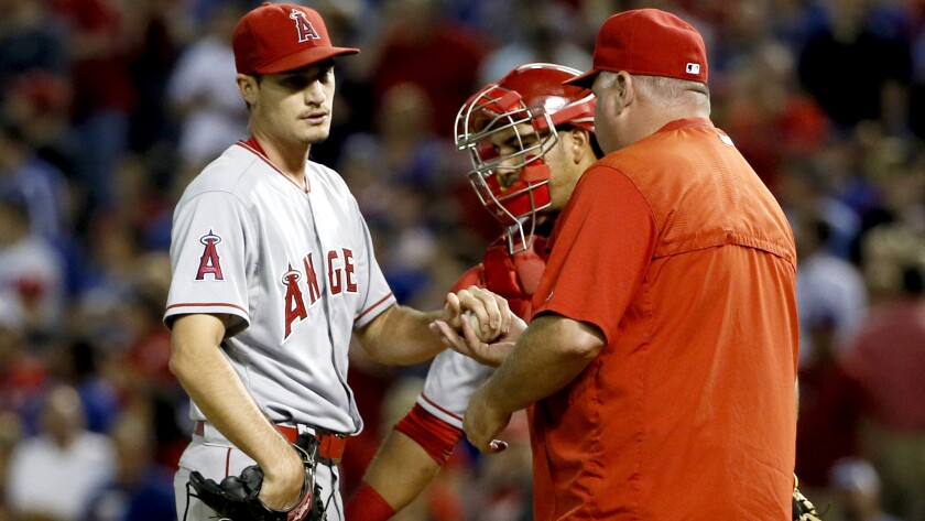 Angels starter Andrew Heaney turns the ball over to Manager Mike Scioscia in the fifth inning Thursday night in Arlington, Texas.