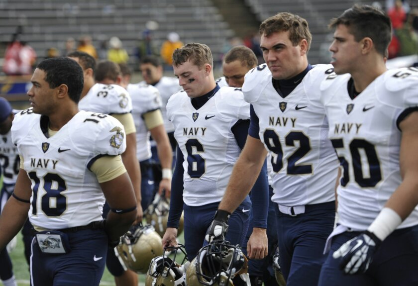 Navy kicker Nick Sloan (6) and his teammate walk off the field after a 45-44 double-overtime loss to Toledo.