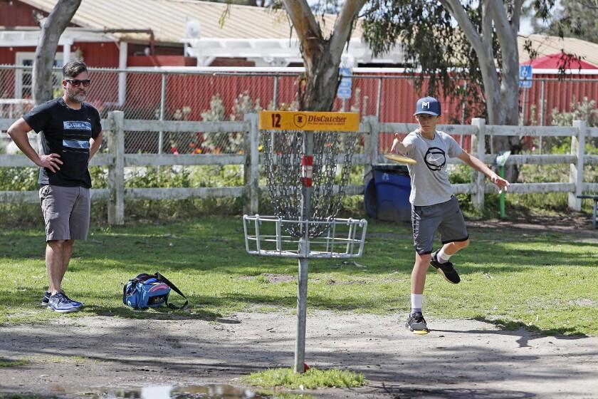 Rob Vermeeren, 44, of Huntington Beach and his son Maddox, 14, play the 12th hole at Huntington Beach Disc Golf Course on Tuesday.