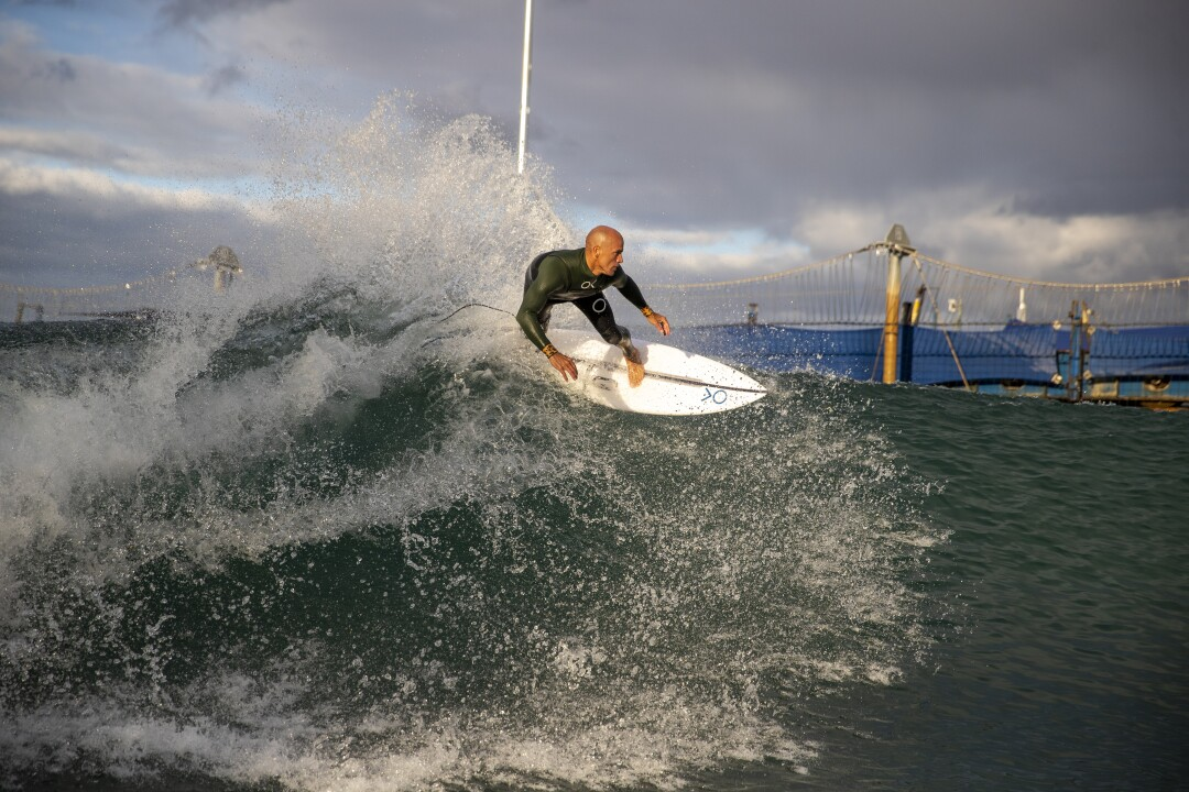 Kelly Slater rides a wave on his surfboard