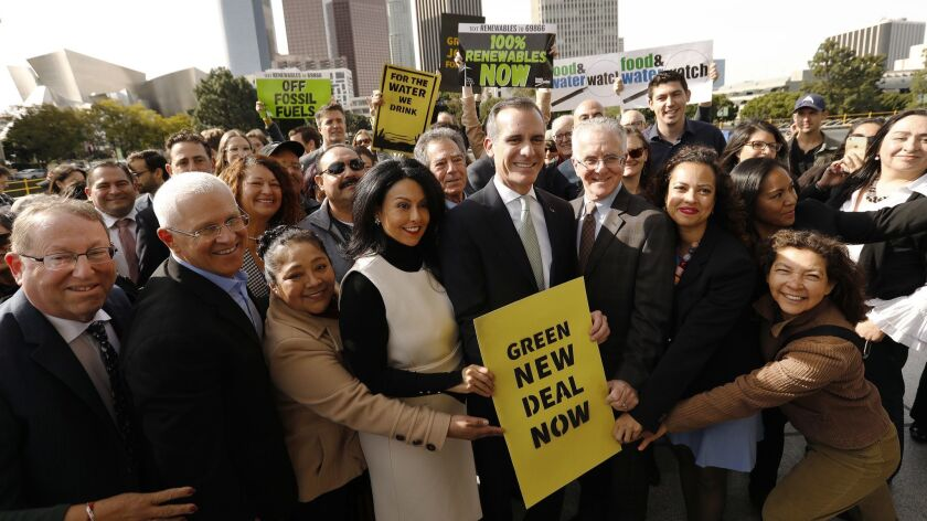 Los Angeles Mayor Eric Garcetti poses for photos after a news conference outside Department of Water and Power headquarters in February.