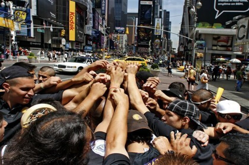 While waiting for their travel visas, members of the Iroquois Nationals Lacrosse team link hands to show team spirit after a brief meeting in New York's Times Square, Monday, July 12, 2010. The 23 players on the Iroquois Indian lacrosse team cannot fly to England for what's considered the Olympics of the sport because the U.S. government won't allow them to re-enter the country on Iroquois nation passports, based on a treaty signed by George Washington. (AP Photo/Bebeto Matthews)
