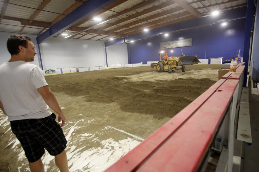 Part owner of a new soon-to-be ice rink, called Ice Town, in Carlsbad, Matt Dunaev, watches Wednesday dirt is distributed in the ice rink. photo by Bill Wechter