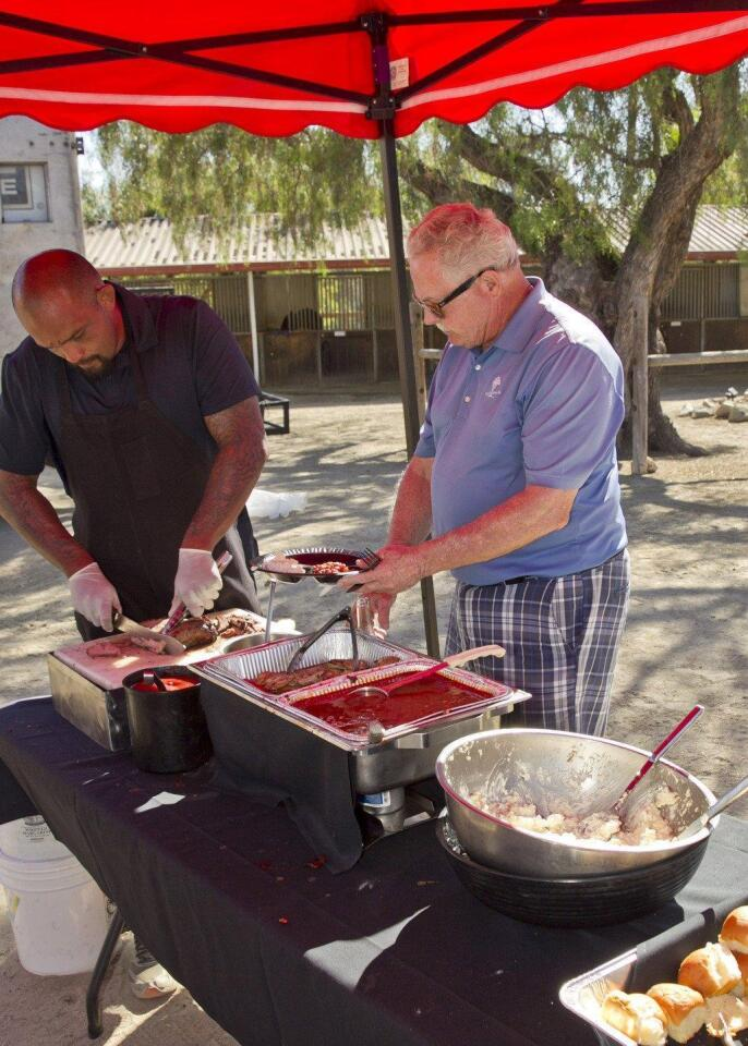 Jose Beltran serves some BBQ to Mike Gallagher