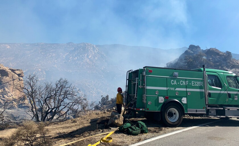 A fire truck and firefighter stand near a smoky canyon.
