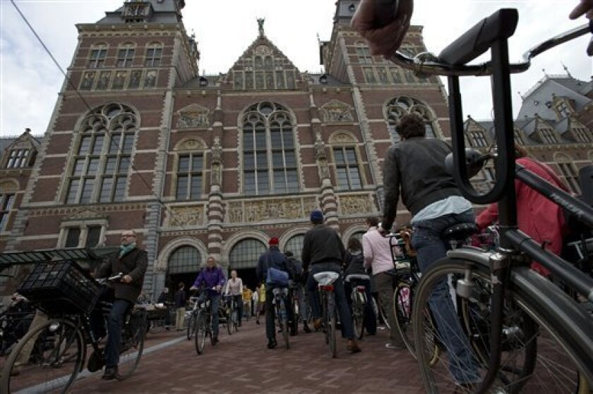 Hundreds of bicycles queue to pass through Rijksmuseum, in Amsterdam, Netherlands, Monday May 13, 2013, signaling the end of more than a decade of efforts by cyclists to ensure a passageway that runs under and through the Rijksmuseum would remain open to bike traffic. The museum, which houses masterpieces by Rembrandt van Rijn and Vincent van Gogh, among others, opened last month after a 10-year renovation. Architects and successive museum directors had opposed allowing bikes through, and a loc