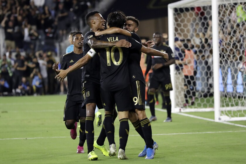 LAFC's Carlos Vela celebrates with teammates after scoring during the second half of Sunday's 3-3 tie with the Galaxy.