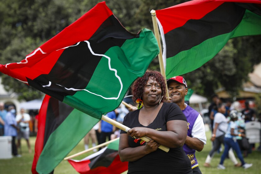 Marla Cooper leads the flag procession for the opening of Juneteenth festivities.