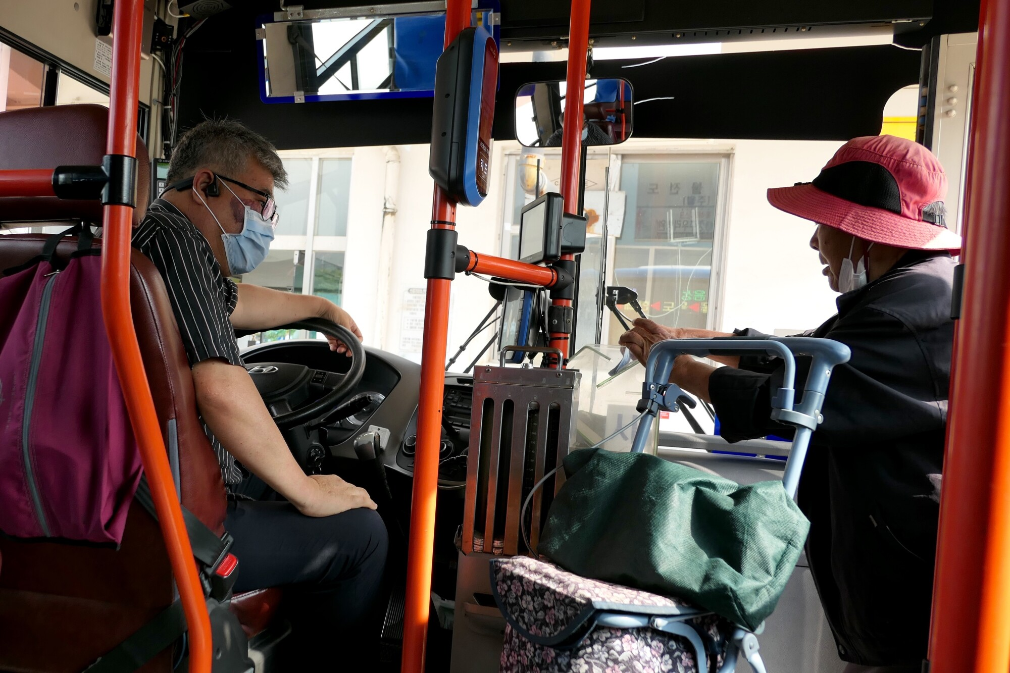 A man sits at the wheel of a bus and a woman pushing a cart gets on board.