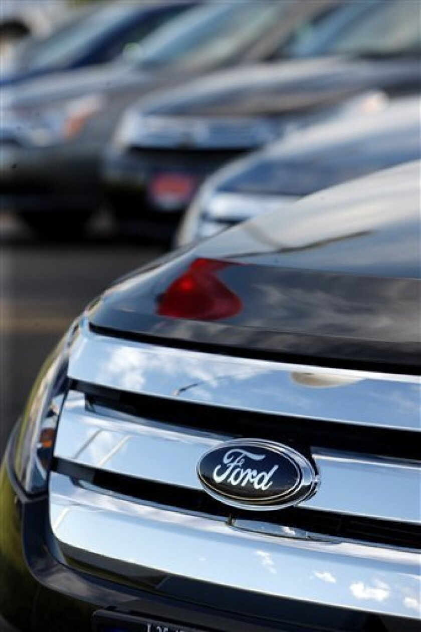 FILE - In this Aug. 2, 2009 file photo, the Ford Co. logo shines on the chromed grille of an 2010 Fusion sedan at a Ford dealership in Denver. Ford Motor Co. said Tuesday, Dec. 1, 2009, U.S. sales held steady in November as buyers snapped up fuel-efficient cars and crossovers. (AP Photo/David Zalubowski, file)