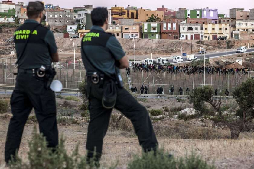 Spanish Guardia Civil watch as would-be immigrants from Africa sit atop a fence after scrambling over two other border barriers on Spain's tiny north African territory of Melilla.