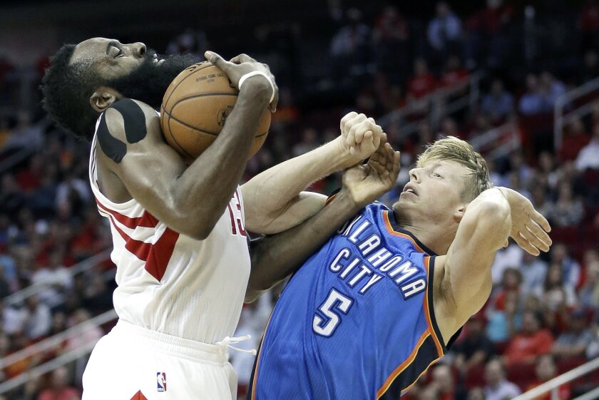 Houston Rockets' James Harden (13) is fouled by Oklahoma City Thunder's Kyle Singler (5) in the second half of an NBA basketball game Monday, Nov. 2, 2015, in Houston. The Rockets won 110-105. (AP Photo/Pat Sullivan)