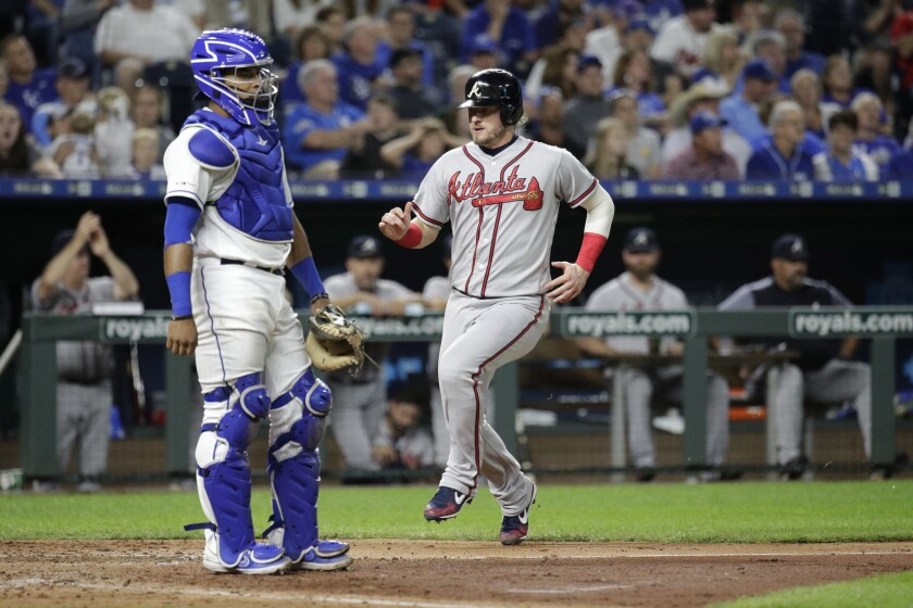 Atlanta Braves' Josh Donaldson crosses the plate past Kansas City Royals catcher Meibrys Viloria to score on a single by Nick Markakis during the fifth inning of a baseball game Wednesday, Sept. 25, 2019, in Kansas City, Mo. (AP Photo/Charlie Riedel)