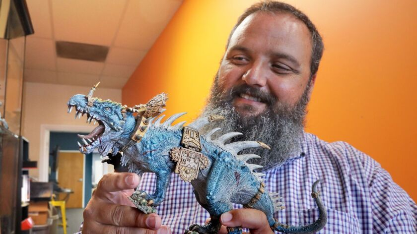 At Gaming on Grand in downtown Escondido, shop owner Ted Apollo holds a model on display there from the Warhammer game series that was expertly painted by one of the shop's customers.