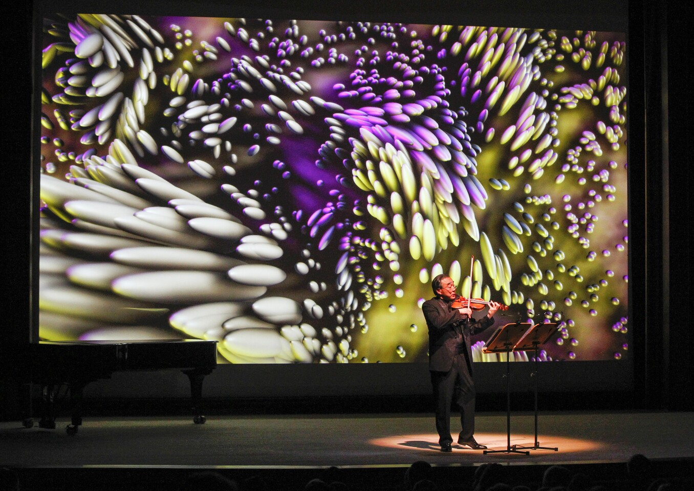 """Violinist Cho-Liang """"Jimmy"""" Lin performs Lalo Schifrin's """"Letters from My Father"""" against a backdrop by creative technologist Osman Koc at the gala opening concert of the La Jolla Music Society's new $82 million Conrad Prebys Performing Arts Center on Friday night in La Jolla, California."""
