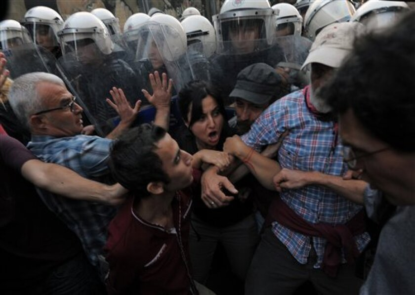 Demonstrators clashes with riot police as they protest the death of Ahmet Atakan in Antakya Monday night, in Istanbul, Turkey, Tuesday, Sept. 10, 2013. Atakan, 22 years old, died Monday night in Antakya after being hit in the head by a teargas canister shot by police during a an anti-government protest, the Atakan family said.(AP Photo)
