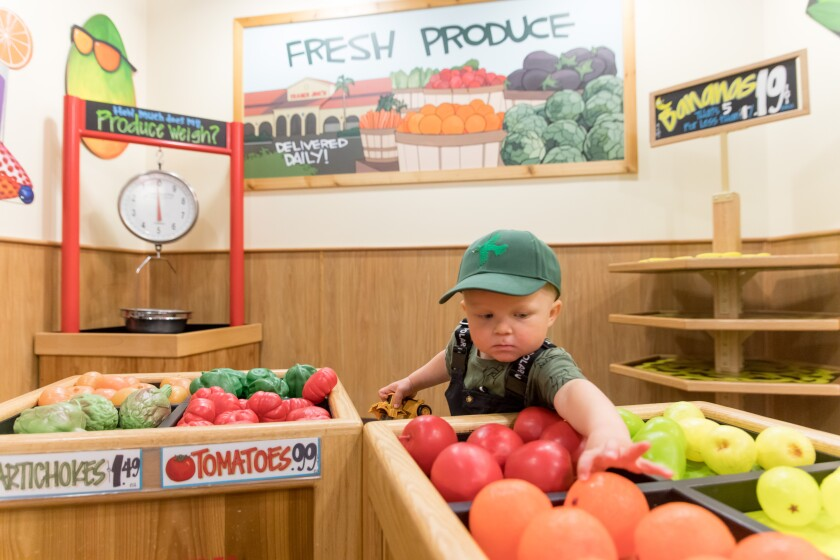 A young shopper eyes the perfect orange at the Trader Joe's exhibit in Pretend City Children's Museum in Irvine. The museum has temporarily closed, but they have been continuing their mission by filming storytime videos and making guides for parents in these trying times.