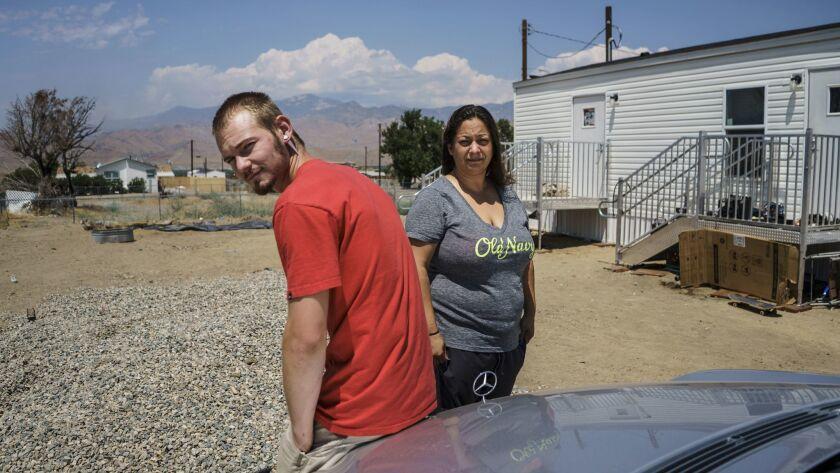 Melanie Perea and her boyfriend, Erik Kirby, outside their makeshift FEMA-provided trailer home in L