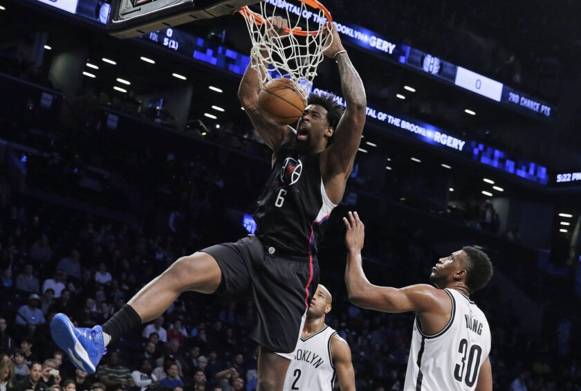 Clippers center DeAndre Jordan dunks the ball in front of Brooklyn forward Thaddeus Young during the first half of a game Dec. 12 at Barclays Center.
