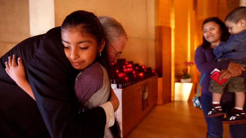 Los Angeles Archbishop Jose Gomez hugs Jersey Vargas, 10, inside the Cathedral of Our Lady of the Angels in Los Angeles in 2014.