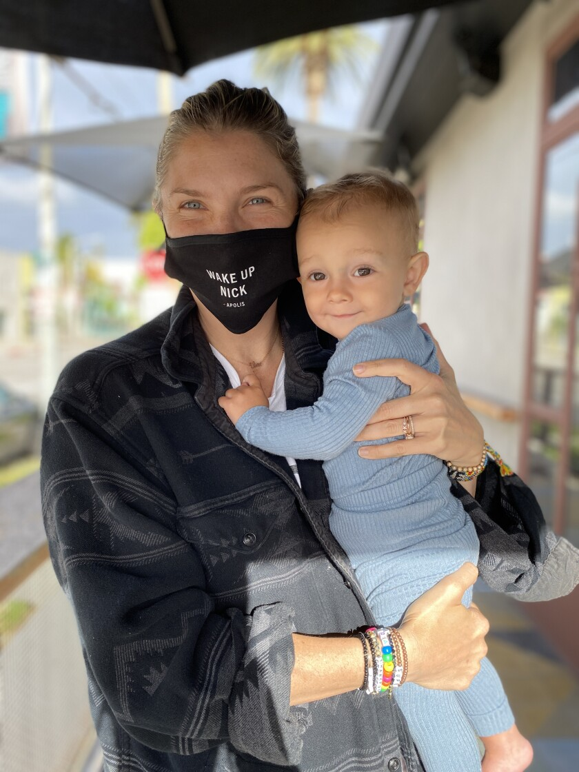 "Amanda Kloots, wearing a ""Wake Up Nick"" mask, holds baby Elvis."
