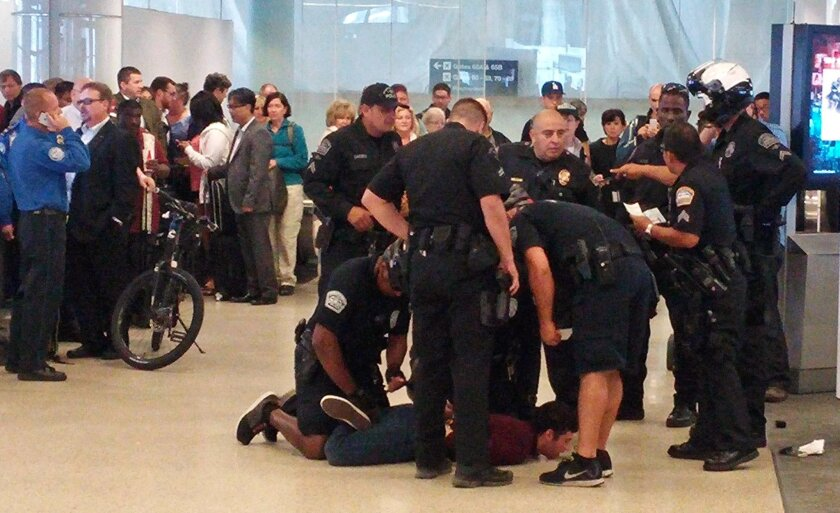Police officers restrain a man they used a stun gun on at Los Angeles International Airport, Wednesday, May 20, 2015. Airport police Sgt. Belinda Joseph said the man who was stunned had refused to cooperate with Transportation Security Administration officers at Terminal 6. (Alex Espinoza via AP)