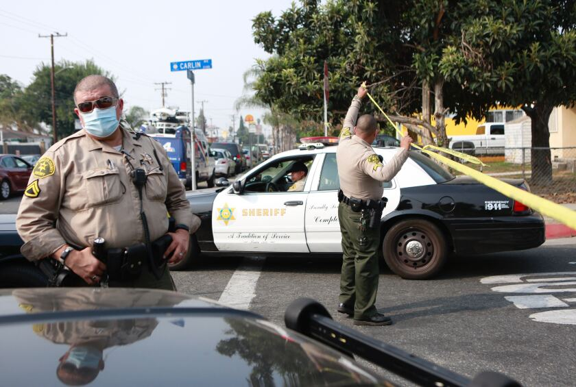 Detectives comb the scene where two L.A. County sheriff's deputies were shot Saturday in Compton, Calif.