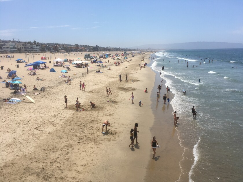 Visitors crowd the beach in Manhattan Beach, Calif., amid the coronavirus pandemic Saturday. Aug. 15, 2020. The heat wave brought dangerously high temperatures, increased wildfire danger and fears of coronavirus spread as people flock to beaches and parks for relief. (AP Photo/John Antczak)