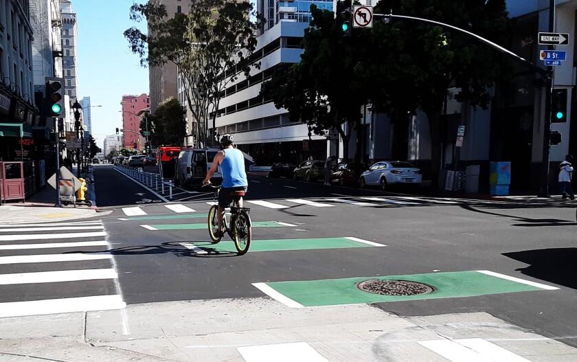 A bike rider uses new bike lanes downtown.