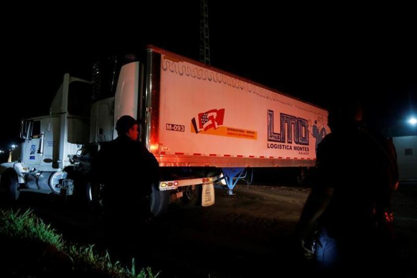 Fotografía donde se muestra a policías Federales que trasladan un contenedor a las instalaciones del Instituto Jalisciense de Ciencias Forenses (IJCF) en el municipio de Tlaquepaque, en el estado de Jalisco (México). EFE