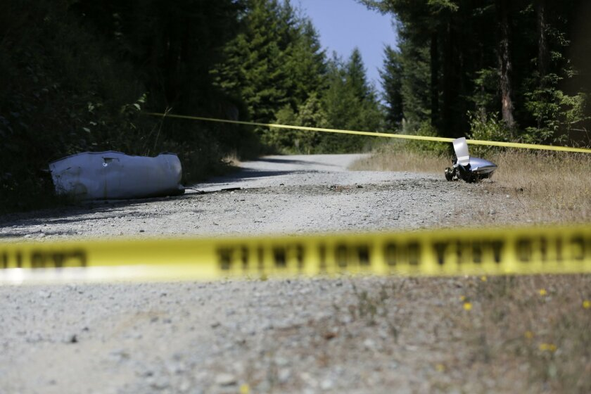 An engine nose cone with a bent propellor blade and other wreckage from a medical transport plane that crashed are shown on a road east of Crannell, Calif., Friday, July 29, 2016. Authorities found the wreckage of a small medical transport plane with four people aboard and confirmed at least two de