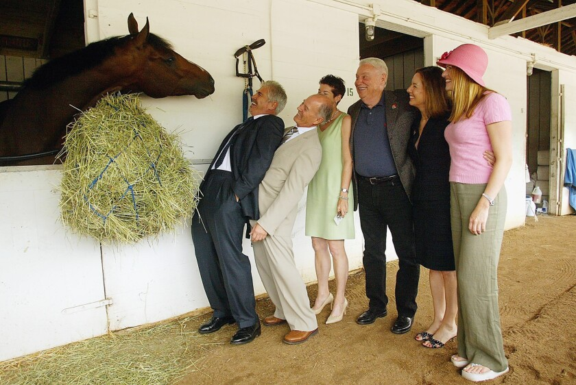 Hughes, center, in 2003, shown at Churchill Downs with a Kentucky Derby contender he was principal owner of
