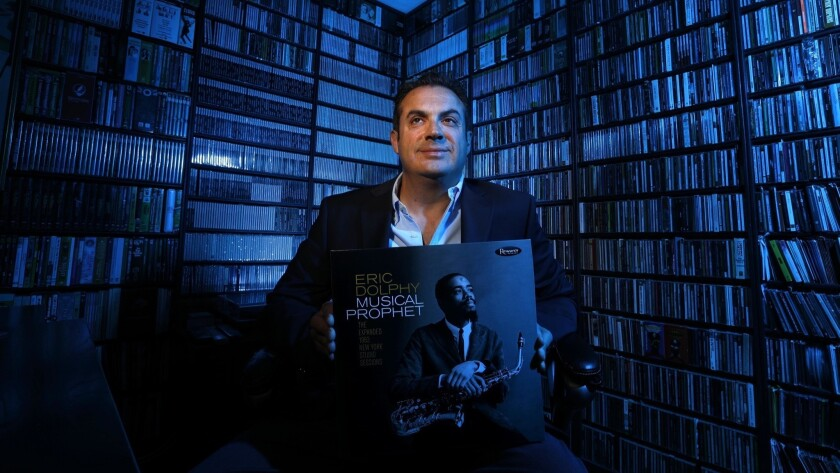 """Zev Feldman, executive vice president and general manager of Resonance Records, holds a copy of his recently produced """"Eric Dolphy: Musical Prophet, against a backdrop of CDs at his Los Angeles office."""