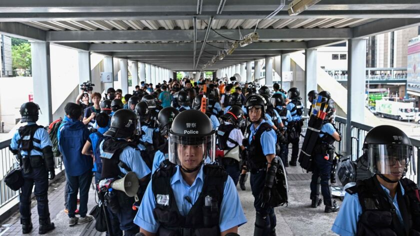 Police in Hong Kong guard a footbridge early Thursday after a violent demonstration against a controversial extradition law proposal.