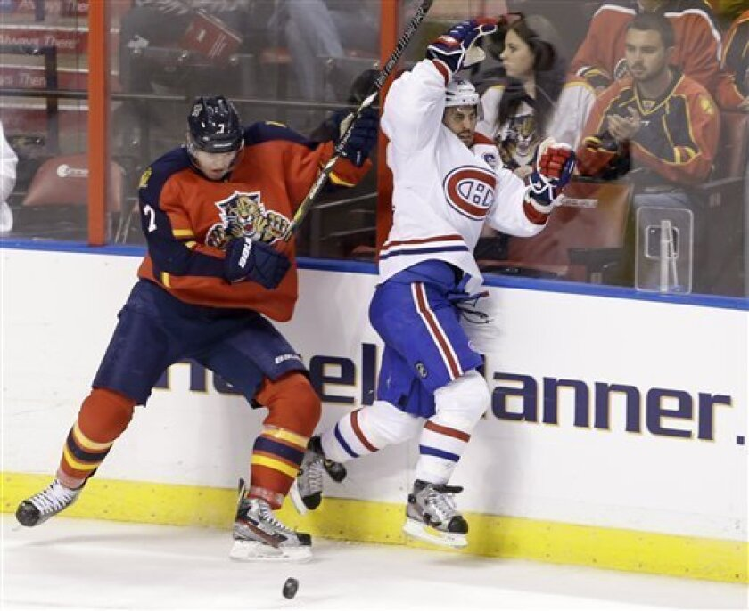Florida Panthers defenseman Dmitry Kulikov, left, of Russia, slams Montreal Canadiens right wing Brian Gionta into the boards during the second period of an NHL hockey game, Thursday, Feb. 14, 2013, in Sunrise, Fla. (AP Photo/Wilfredo Lee)