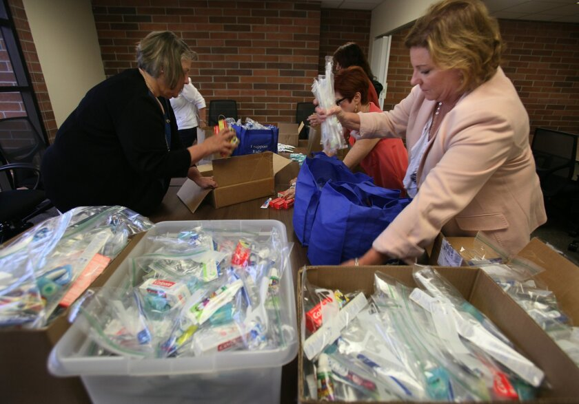 Cheryl Steinholt, right, puts hygiene kits into a carrying bag after she and fellow auxiliary member have finished assembling the kits. Members of the Rady Children's Hospital Auxiliary regularly assemble toiletry and dental kits for parents who might find themselves unprepared when their childr