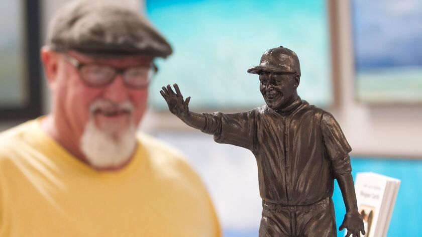 Artist Randy Morgan stands near his model of Skipper Carrillo at the Forest & Ocean Gallery. Gallery owner Ludo Leideritz and Morgan have kick-started a fundraising effort for a life-sized statue of Carrillo, a devoted volunteer at Laguna Beach High.