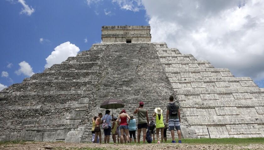 Tourists are dwarfed by El Castillo at the Chichen Itza ruins in Yucatan, Mexico.