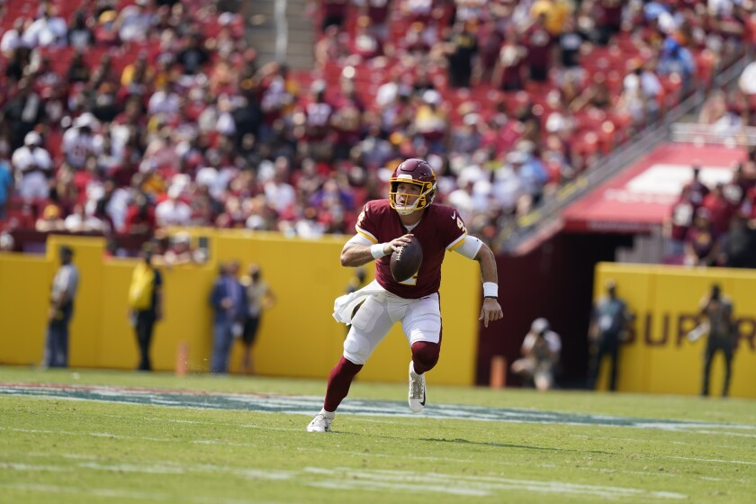 Washington Football Team quarterback Taylor Heinicke (4) running with the ball during the first half of an NFL football game against the Los Angeles Chargers, Sunday, Sept. 12, 2021, in Landover, Md. (AP Photo/Alex Brandon)