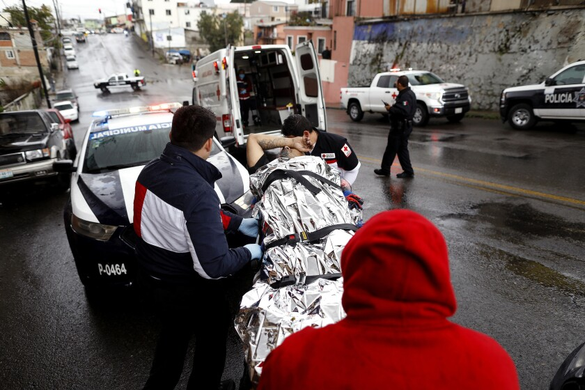 Paramedics with Tijuana Red Cross prepare to transport a shooting victim to Tijuana General Hospital.