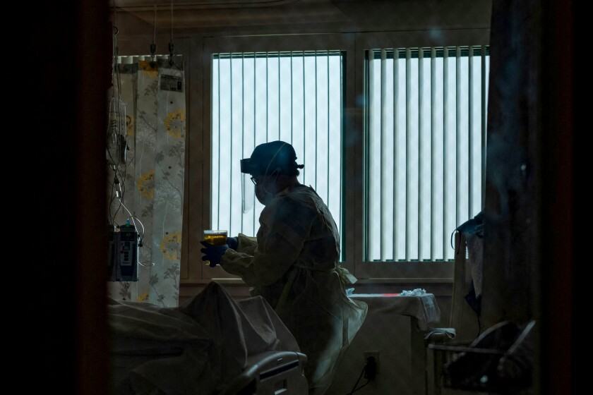 A nurse cares for a Covid-19 patient