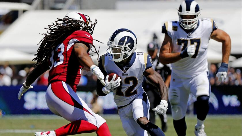 Rams wide receiver Brandin Cooks (12) makes a cut to avoid the tackle of Arizona Cardinals defensive back Tre Boston (33) in the first half at the Coliseum on Sept. 16, 2018.