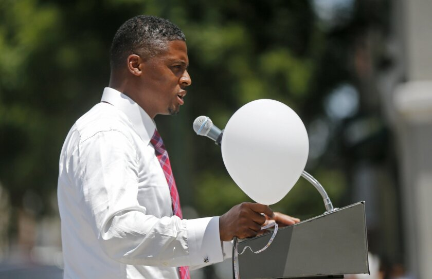 Former NFL running back Warrick Dunn speaks at a noon vigil organized by municipal court workers in downtown Baton Rouge, La., Wednesday, July 20, 2016, in honor of recent slain and injured sheriff deputies and police His mother, Baton Rouge police officer Betty Smothers, was killed during a robbery attempt in 1993, when he was 18. Multiple police officers and sheriff deputies were killed and wounded Sunday morning in a shooting near a gas station in Baton Rouge, less than two weeks after a black man was shot and killed by police here, sparking nightly protests across the city. (AP Photo/Gerald Herbert)